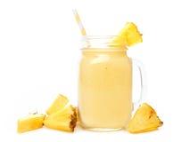 在一个金属螺盖玻璃瓶的菠萝圆滑的人有在白色的果子切片的 免版税库存照片