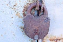 在一个金属门的老生锈的挂锁与破裂的蓝色油漆 免版税库存照片