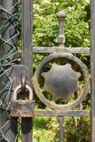 在一个金属门的老生锈的锁到庭院里 锁在铁门 标志监禁和奴隶制 物产安全链 免版税库存图片