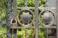 在一个金属门的老生锈的锁到庭院里 锁在铁门 标志监禁和奴隶制 物产安全链 免版税库存照片