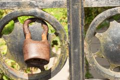 在一个金属门的老生锈的锁到庭院里 锁在铁门 标志监禁和奴隶制 物产安全链 库存图片