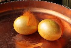 在一个金黄盘子的两个黄色鸡鸡蛋 免版税库存图片