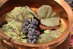 在一个金黄碗的紫色葡萄 免版税库存图片