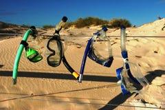 在一个铁丝网的潜航的齿轮干燥在海滩的蓝天下 免版税图库摄影