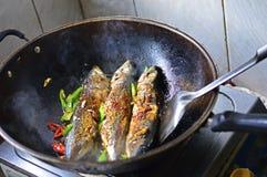 在一个铁锅油煎的中国家庭烹饪鱼用绿色和红色辣椒 免版税库存图片