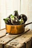 在一个铜浸染工的紫色微型茄子在葡萄酒木箱子,秋天收获,地中海烹调 免版税库存照片