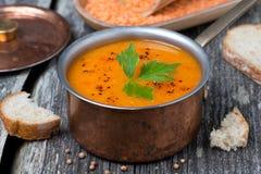 在一个铜罐的辣红色小扁豆汤在一张木桌上 免版税图库摄影