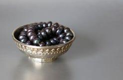 在一个银色杯子的黑珍珠 库存图片