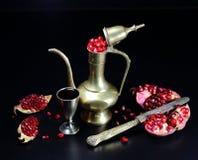 在一个银色蒸馏瓶和一块玻璃的石榴用石榴石汁液 图库摄影