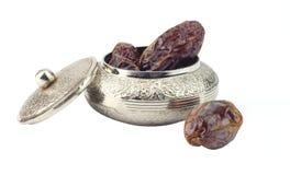 在一个银色首饰碗的枣椰子 免版税库存照片