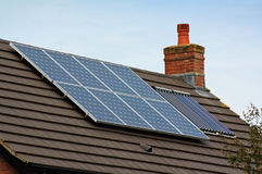 在一个铺磁砖的屋顶的光致电压的太阳电池板 免版税库存照片
