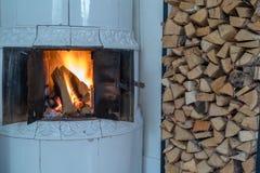 在一个铺磁砖的火炉的火与白色瓦片 免版税图库摄影