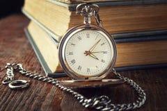 在一个链子的葡萄酒手表在旧书背景  免版税库存图片