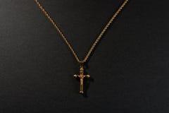 在一个链子的金十字架在黑背景 免版税库存照片