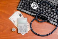 在一个键盘的听诊器有计算器的 图库摄影