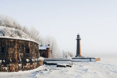 在一个镇静和落寞冬天风景的灯塔 白色粉刷了在蓝天的灯塔与云彩 免版税库存图片