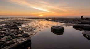 在一个镇静岩石水池的日落在英国海滩 免版税库存图片