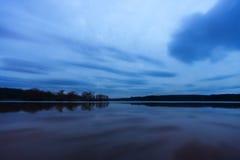 在一个镇静湖的深刻的蓝色和紫色日落,距离的m土地 库存照片