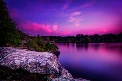 在一个镇静湖的紫罗兰色日落 免版税库存图片
