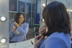 在一个镜子前面的妇女在化装室 免版税库存图片