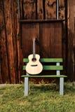 在一个长木凳的吉他 免版税库存图片