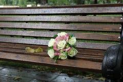 在一个长木凳的婚礼花束在公园 免版税图库摄影