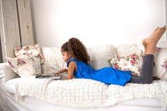 在一个长沙发的黑十几岁的女孩选址有膝上型计算机的 免版税库存图片