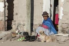 在一个门前面的未认出的玻利维亚的年长妇女与一条狗在Jirira村庄在`芸香Intersalar `奥鲁罗的 免版税库存图片