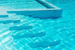 在一个闪耀的蓝色水池的水下的步 免版税库存照片