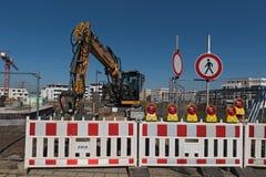 在一个闭合的建造场所入口后的黄色轮子装载者在Riedberg新的区  库存图片