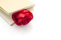 在一个闭合的笔记本的红色玫瑰在白色背景 库存图片