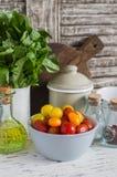 在一个陶瓷碗、绿色庭院草本、橄榄油和香料的新鲜的蕃茄在轻的土气木背景 免版税库存照片