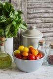 在一个陶瓷碗、绿色庭院草本、橄榄油和香料的新鲜的蕃茄在轻的土气木背景 库存照片