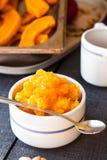 在一个陶瓷碗的南瓜纯汁浓汤有匙子的,健康点心 免版税库存图片