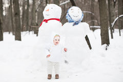 在一个雪人旁边的滑稽的婴孩在冬天公园 免版税库存图片