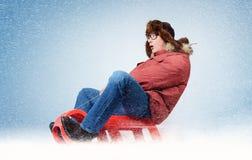 在一个雪撬的滑稽的人飞行在雪,概念冬天乐趣 免版税库存图片