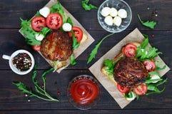 在一个面包的水多的汉堡与芝麻菜、无盐干酪和蕃茄的在黑暗的木背景 图库摄影
