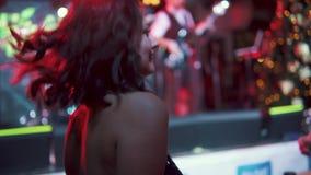 在一个音乐会的年轻有吸引力的妇女跳舞在多彩多姿的灯光芒的阶段附近  回到视图 股票视频
