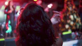 在一个音乐会的年轻有吸引力的妇女跳舞在多彩多姿的灯光芒  回到视图 影视素材