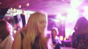在一个音乐会的年轻有吸引力的妇女跳舞在多彩多姿的灯光芒  影视素材