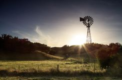 在一个领域的一台老风车在日落 免版税图库摄影