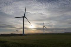 在一个领域的两个风轮机剪影在日落 免版税库存图片