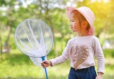 在一个领域的可爱的矮小的亚洲女孩穿戴草帽与昆虫网在夏天 r 免版税库存图片