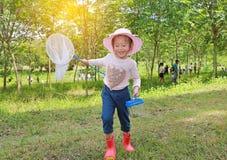 在一个领域的可爱的矮小的亚洲女孩穿戴草帽与昆虫网在夏天 r 库存照片