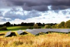 在一个领域的太阳电池板在农村秋天在温暖环境美化 库存图片