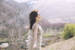 在一个风景的年轻美好的女性模型与山和v 库存照片