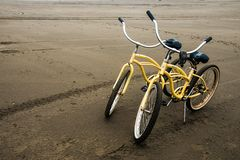 在一个风雨如磐的秋天晚上期间,两在沙子海滩的自行车长滩华盛顿 免版税库存图片