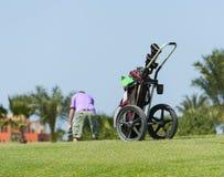 在一个高尔夫球场的小型运车有高尔夫球运动员的 库存图片