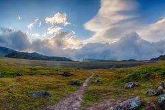 在一个高山草甸的美好的日落以石小山为目的 免版税库存照片
