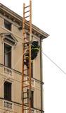 在一个高木楼梯的无所畏惧的消防队员 免版税图库摄影